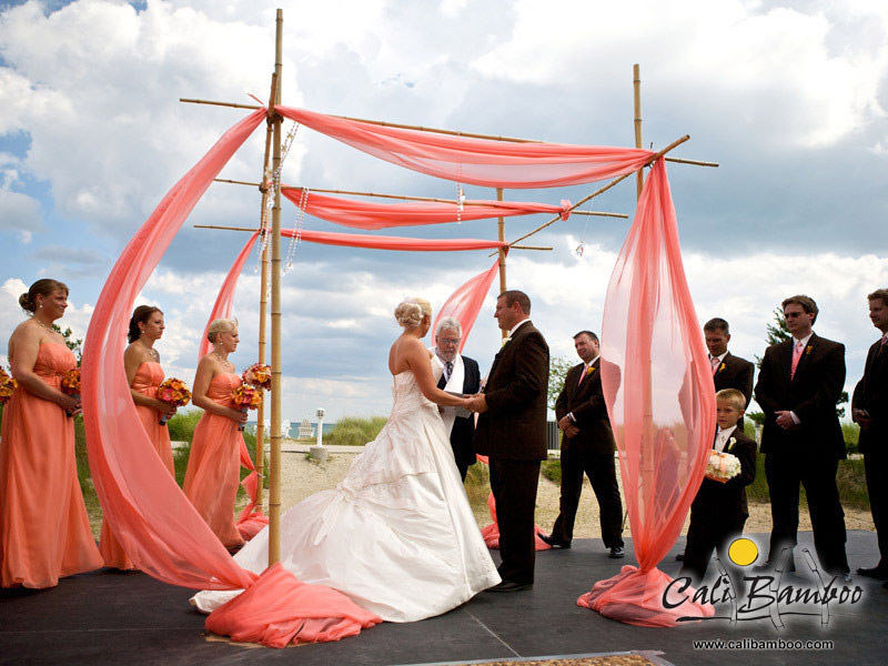 This flowing, coral-themed bamboo arbor is accented with hanging pearls and naturally includes the rest of the wedding party.